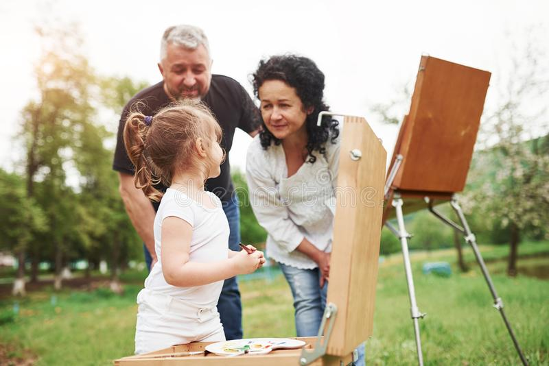 You`re doing it good. Grandmother and grandfather have fun outdoors with granddaughter. Painting conception.  royalty free stock photography