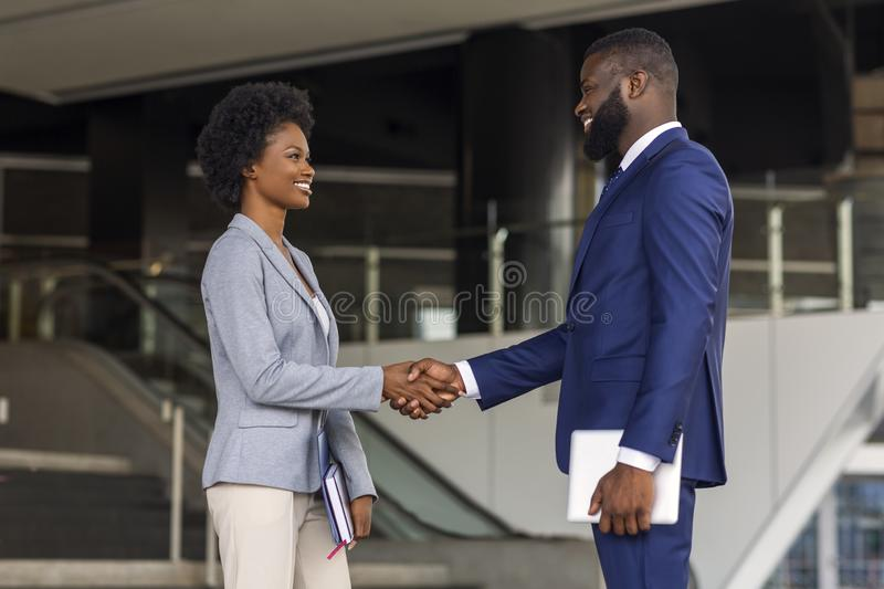 You`re hired. Business people shaking hands near office building. You`re hired. African American business people shaking hands near office building after job royalty free stock images