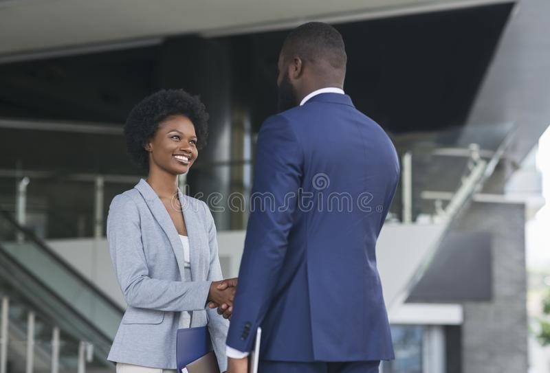 You`re hired. Business people shaking hands near office building. You`re hired. African American business people shaking hands near office building after job stock image