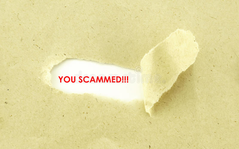 YOU SCAMMED. Text YOU SCAMMED appearing behind torn light brown envelope royalty free stock photography