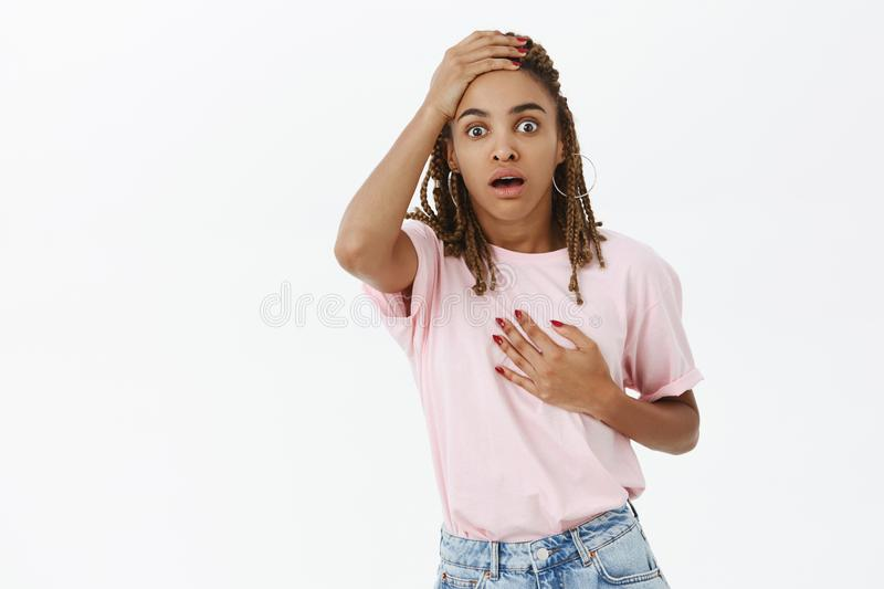 You scared me to death. Portrait of shocked speechless cute dark-skinned young female holding hand on dreads and heart royalty free stock image