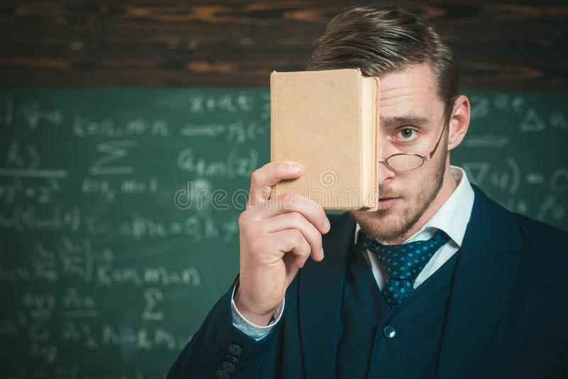You should remember. Teacher formal wear and glasses looks smart, chalkboard background. Man unshaven holds book in. Front of face. Teacher insists on need to royalty free stock photos