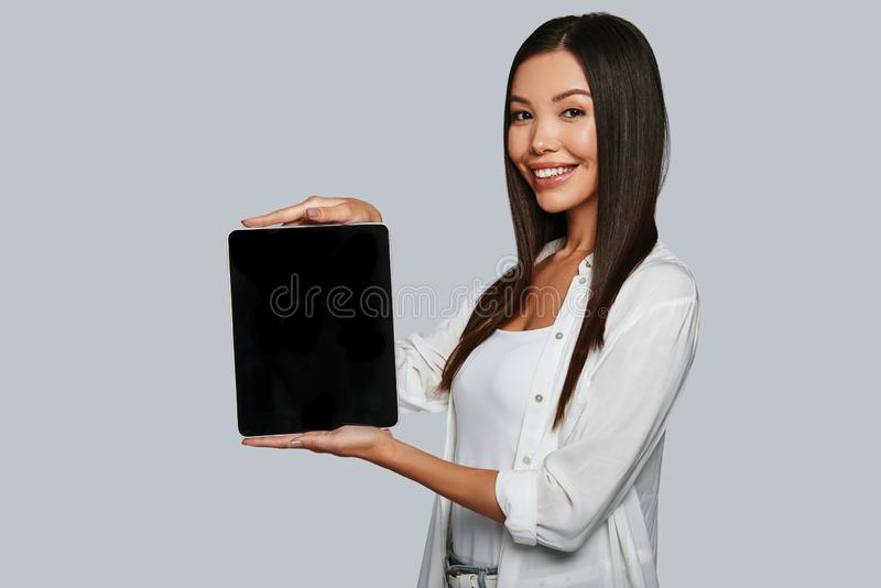 You should see this. Attractive young Asian woman pointing copy space on her digital tablet and smiling while standing against grey background stock images