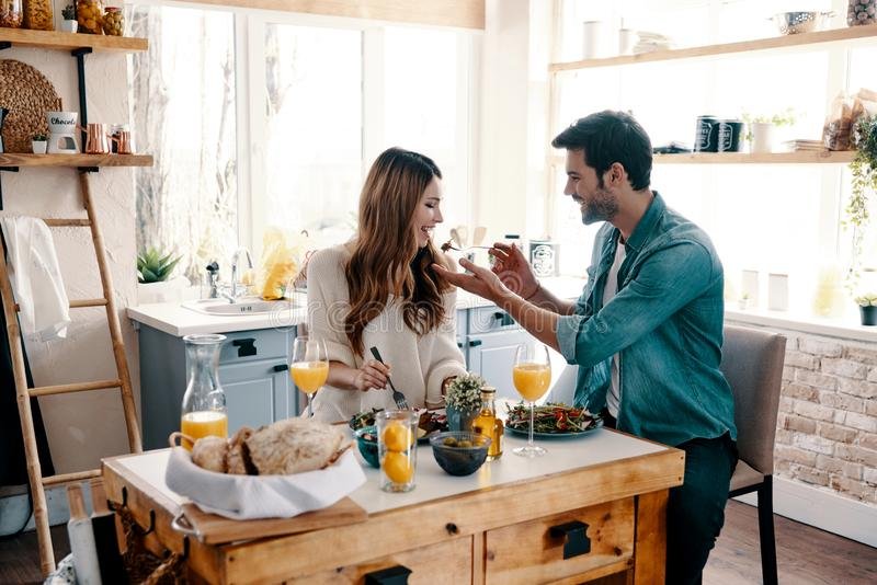 You should taste it!. Beautiful young couple enjoying healthy breakfast while sitting in the kitchen at home royalty free stock photo