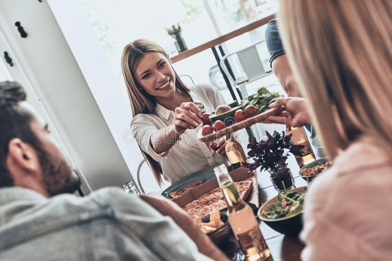You should try it!. Group of young people in casual clothing eating and smiling while having a dinner party indoors stock images