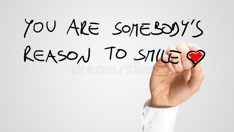 You are somebody's reason to smile. Man writing a beautiful motivational or spiritual message - You are somebody's reason to smile - with a red heart at the end stock photo