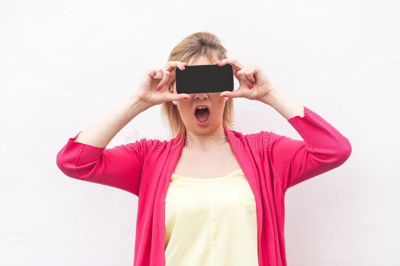 Are you sure? Portrait of shocked young woman in pink blouse standing, holding and covering eyes with smartphone, like eyeglasses stock images
