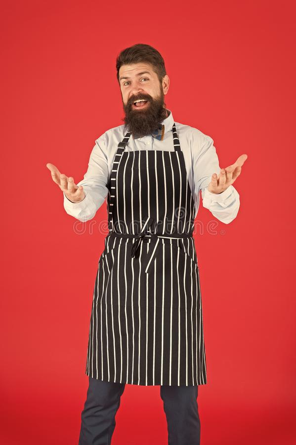 You are welcome. Bearded man with greeting gesture wearing bib apron. Cheerful man cook with beard and mustache in stock photo