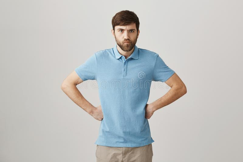 You will be punished. Studio shot of angry cute caucasian guy with beard and moustache holding hands on waist, sulking royalty free stock photo
