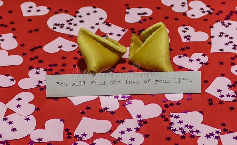 `You will find the love of your life` message in broken fortune cookie on red background covered with harts royalty free stock image