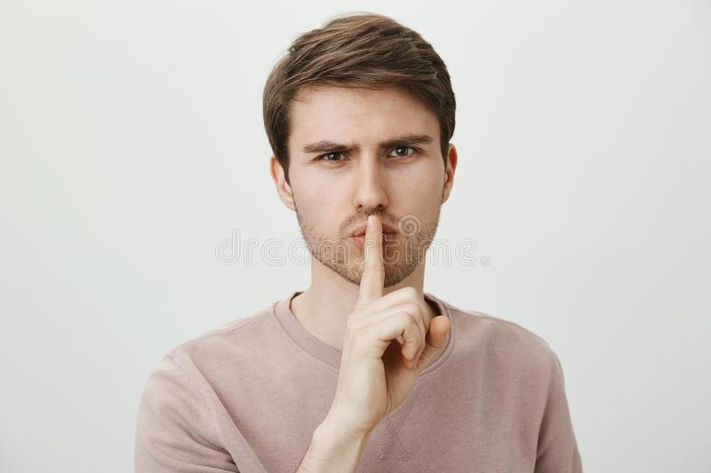 You will keep mouth shut about out business. Portrait of strict serious man with confident expression, standing against. Gray background, showing shh or shush royalty free stock photography