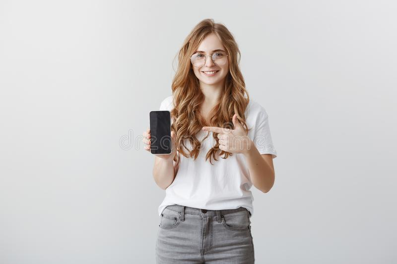 You would not find phone better. Satisfied good-looking shop assistant in trendy transparent glasses showing smartphone. Pointing at device with index finger royalty free stock photo
