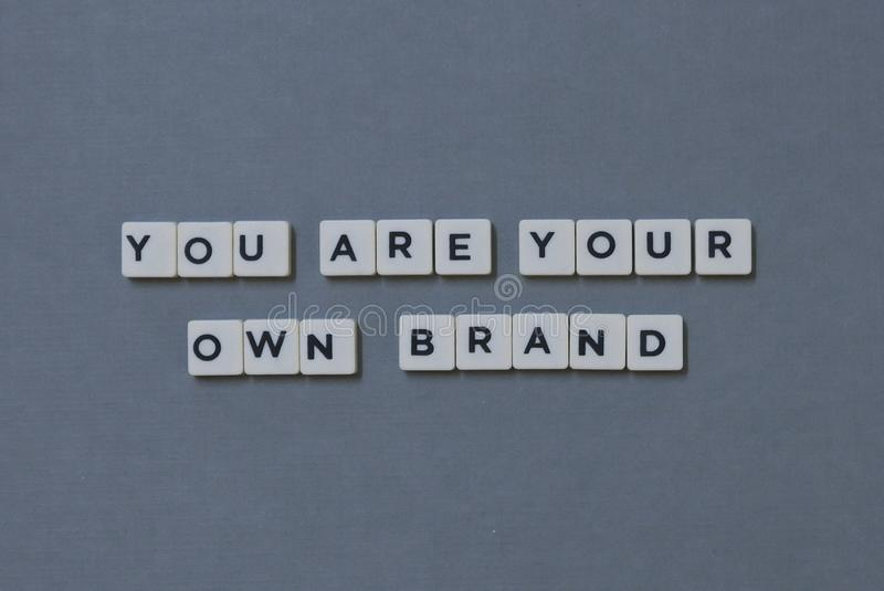 ' You Are Your Own Brand ' word made of square letter word on grey background. Business, success, marketing, career, new, personal, confidence royalty free stock photography
