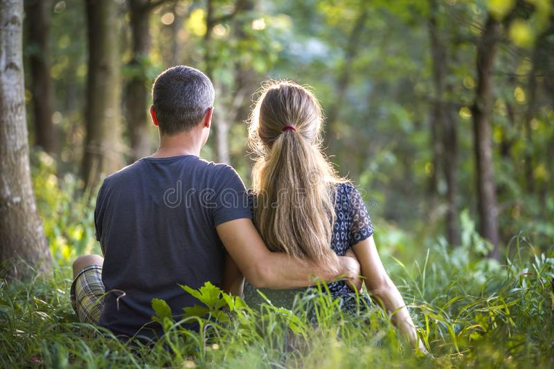 Youg couple, man and a woman sitting together outdoors enjoying nature stock photos