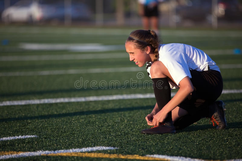 Youg soccer girl lacing shoes on the field stock photography