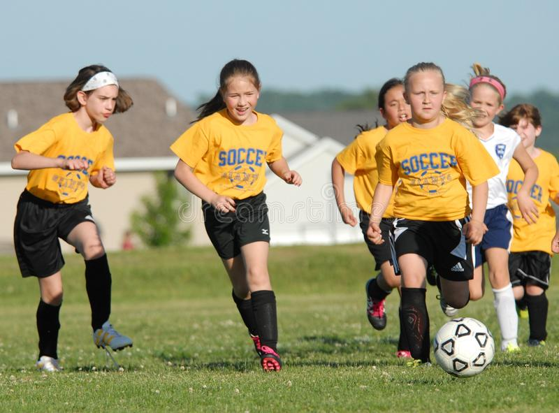 A youg soccer player controls the ball as she races for the goal. stock photo