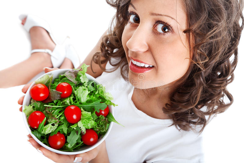 Youg woman eating healthy salad. Isolated on white background stock photos