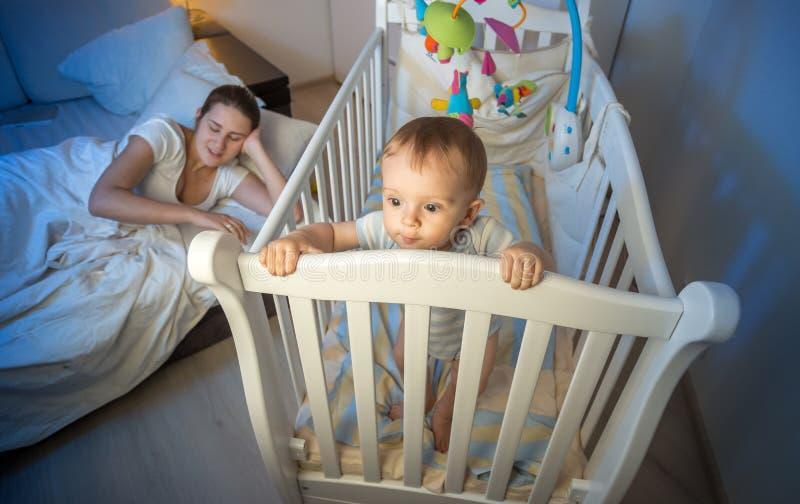 Yougn母亲睡着了,当她站立在轻便小床时的失眠的婴孩 图库摄影