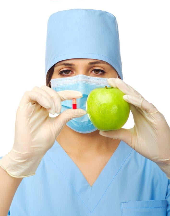Yougn manipulerar med pillen och äpplet royaltyfria foton