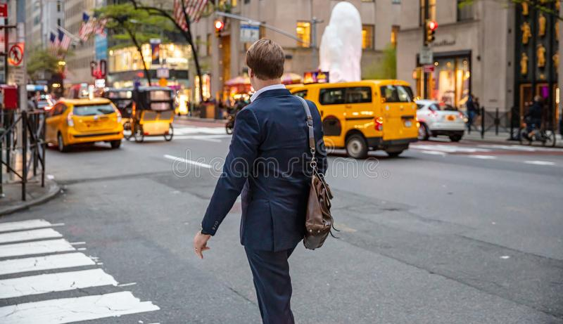 Youmg礼服的人穿过街道在纽约曼哈顿 免版税图库摄影