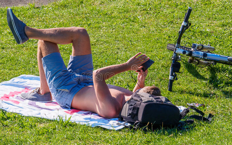 Youn Man Sunbathing Looking am Handy lizenzfreie stockbilder