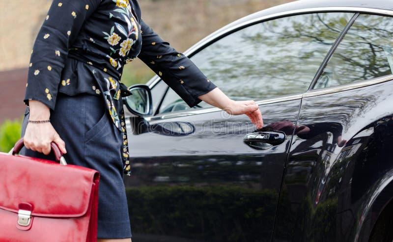 Youn volwassen elegante vrouw met rode koffer open deur in luxe c stock afbeelding