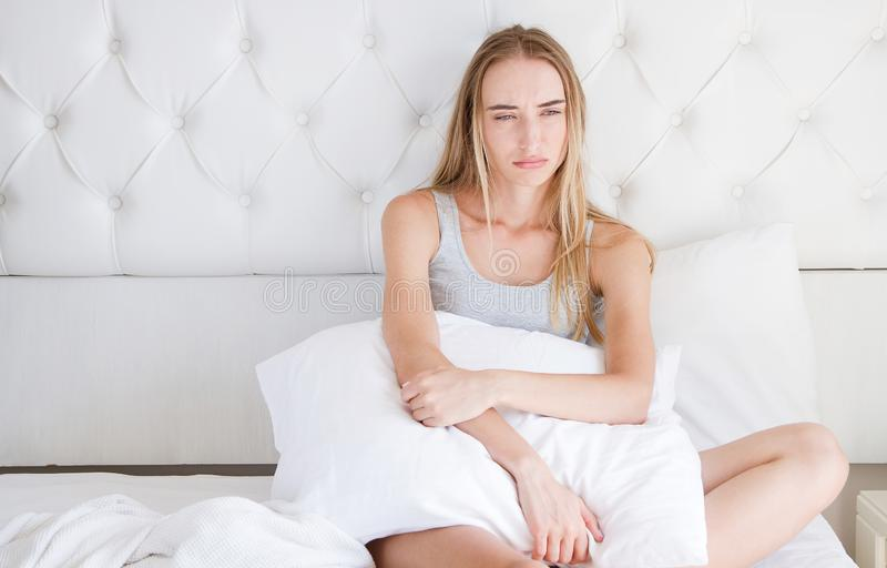 yound哀伤的妇女画象说谎在床上的在轻的屋子,失眠,宿酒里 库存图片