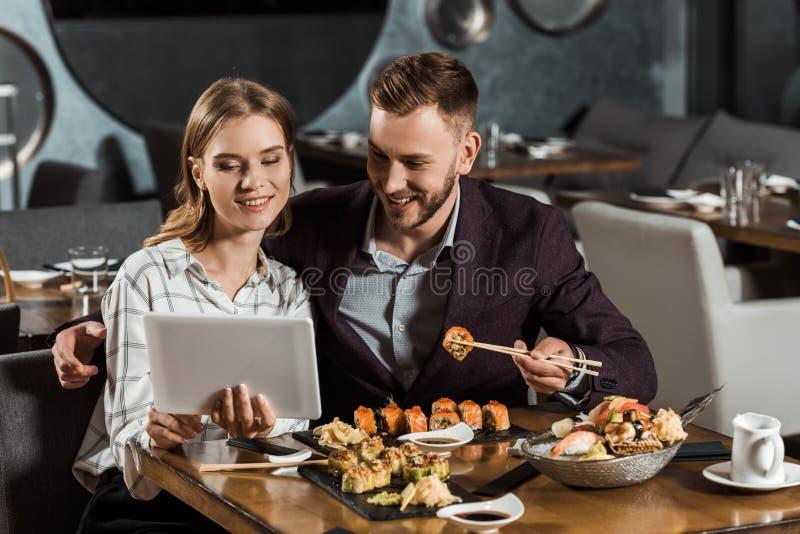 yound成人有吸引力的夫妇使用数字片剂的,当吃寿司时 免版税库存照片