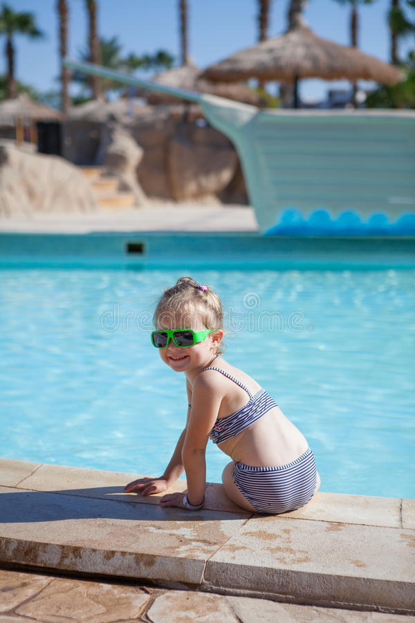 Yound child sit on swimming pool stock photo