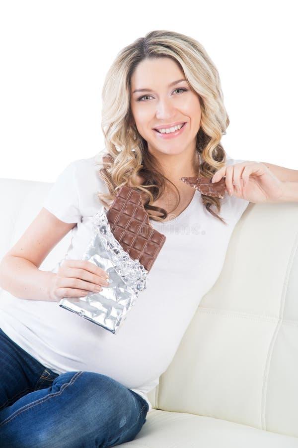 Yound ciężarni blondyny ma kąsek czekoladowy bar fotografia royalty free