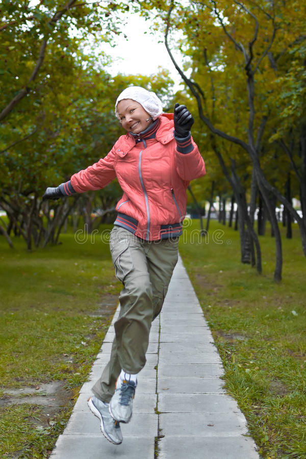 Yound-Frau in der roten Jacke springt und hat einen Spaß lizenzfreie stockfotos