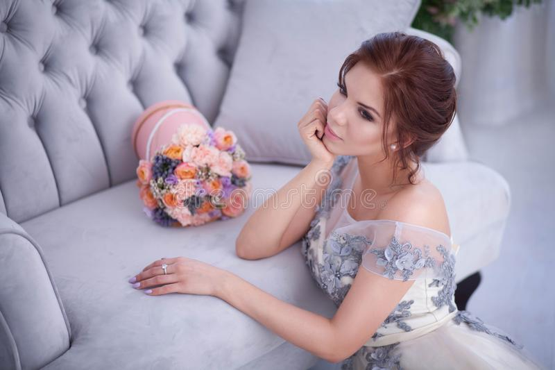 Yound-Frau, die auf blauem Sofa sich entspannt lizenzfreie stockfotografie