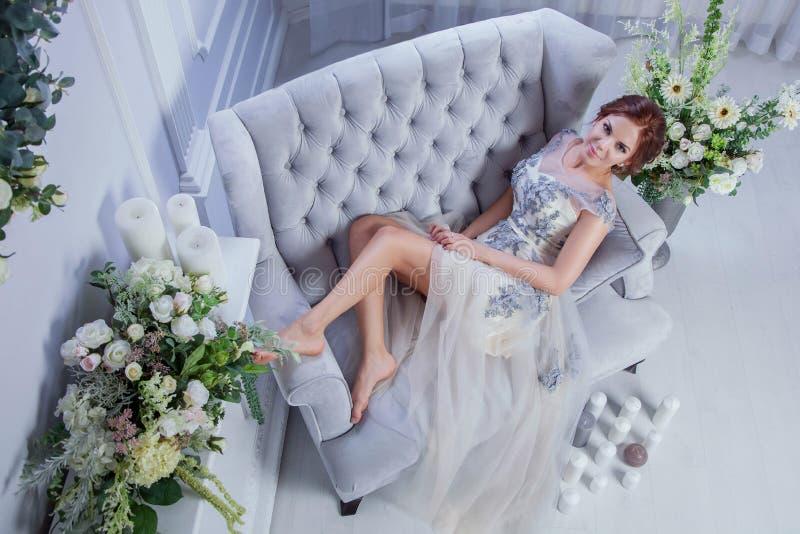 Yound-Frau, die auf blauem Sofa sich entspannt stockfotos