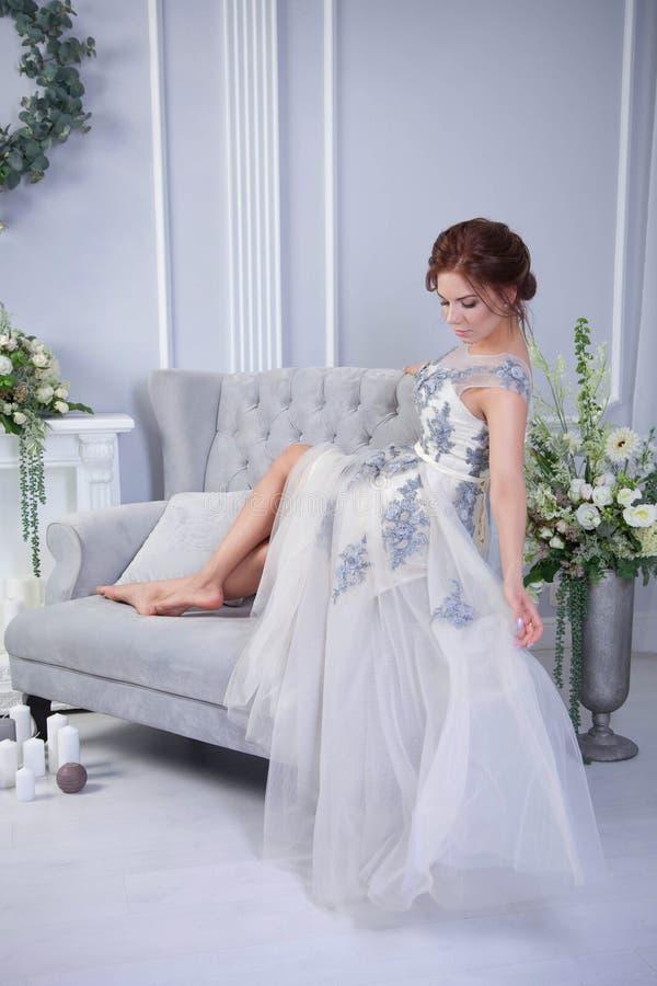Yound-Frau, die auf blauem Sofa sich entspannt lizenzfreies stockbild