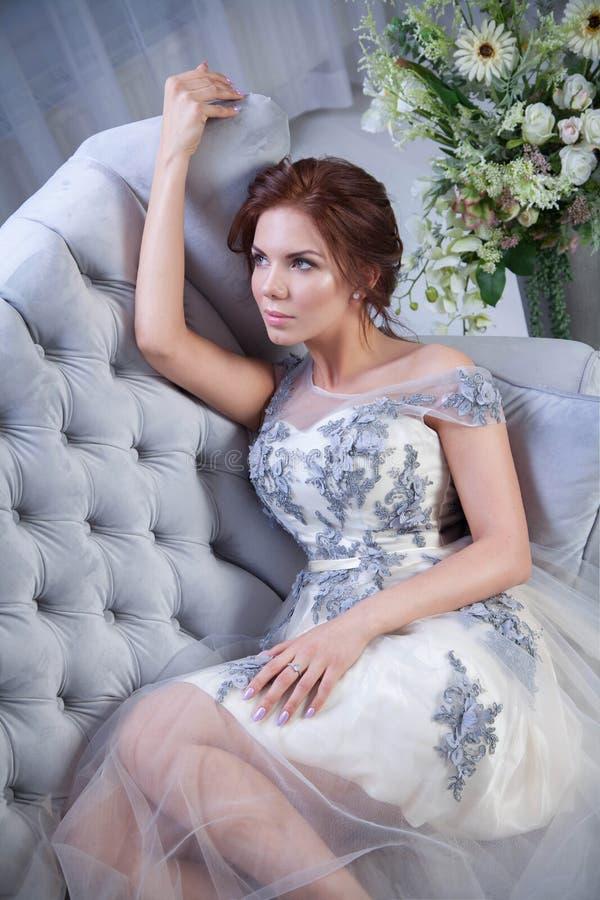 Yound-Frau, die auf blauem Sofa sich entspannt stockbild