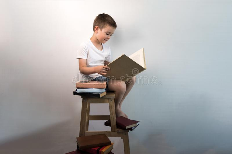 Yound kid reading interesting book at the wooden chair near white wall. Concept of reading an interesting and exciting book everyw. Here stock images