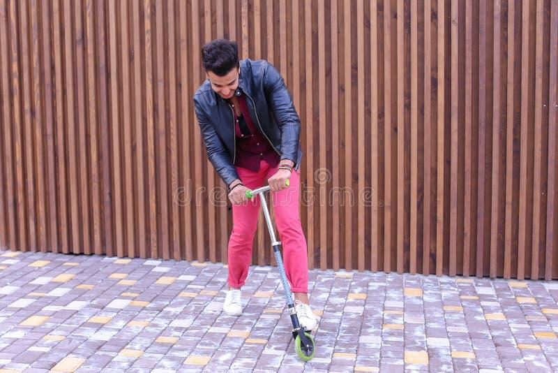 Yound masculino árabe atractivo Guy Rides Scooter, diversión y fotos de archivo libres de regalías