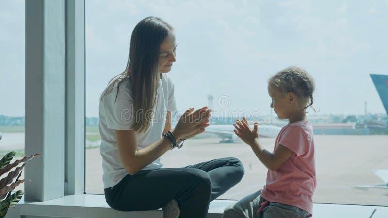 Yound moder och liten gullig dotter som har gyckel på flygplatsen arkivbilder