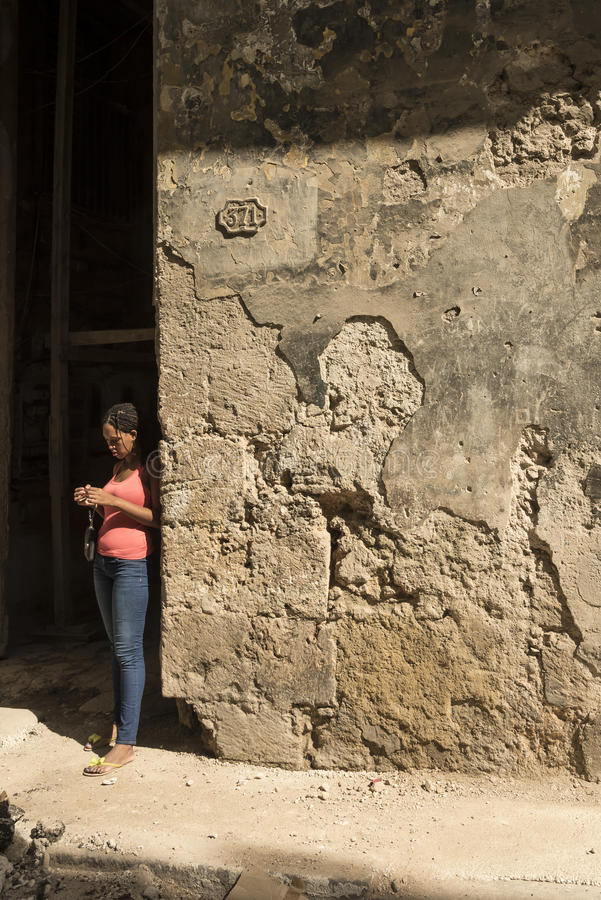 Yound woman standing by worn wall Havana stock images