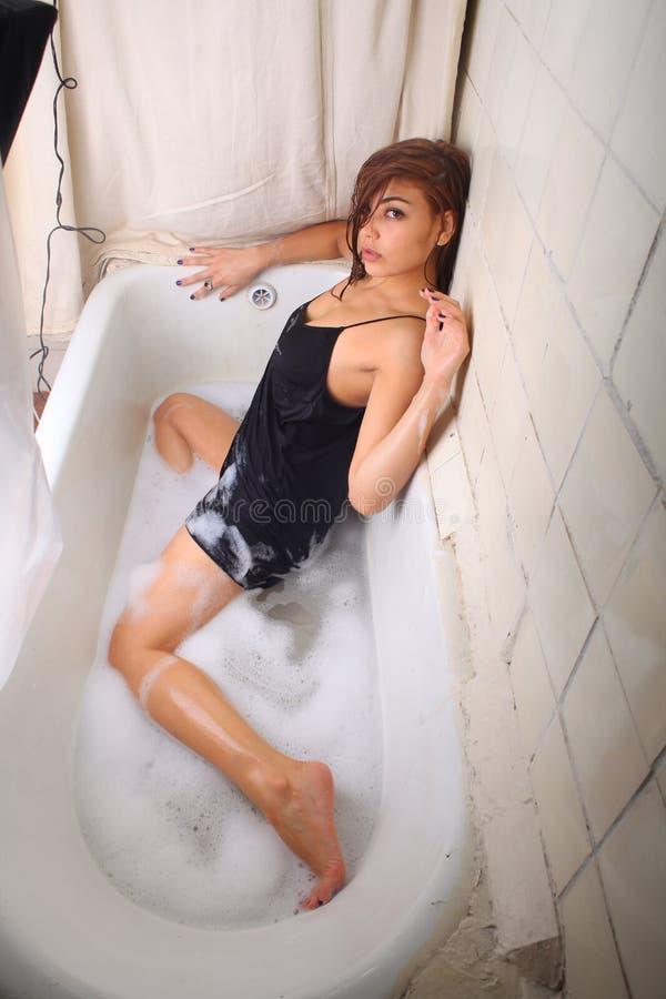 Younf-Schönheit mit den langen Beinen und dem schwarzen Haar im Badezimmer und im Schaum lizenzfreie stockfotos