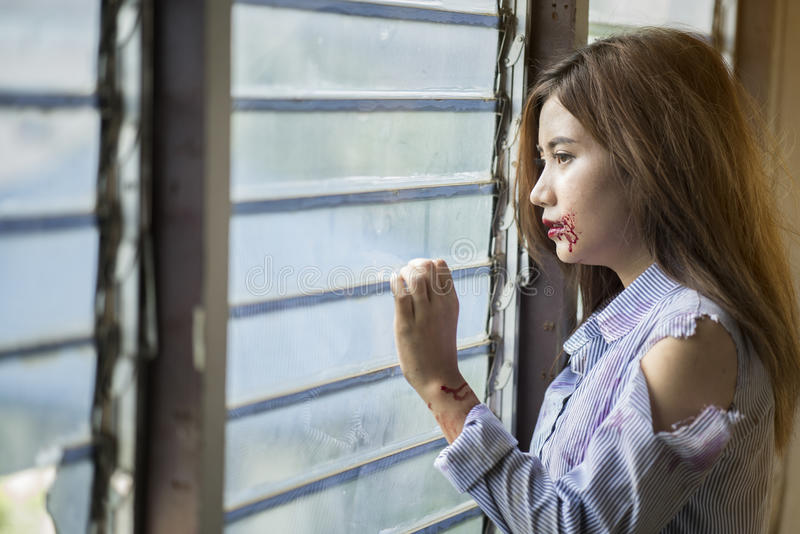 Young abused woman scared looking through the window seeking safety. Young abused woman scared looking through the window seeking safety, emotion and feeling royalty free stock photography