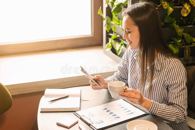 Young accountant making financial report in cafe, stock photo
