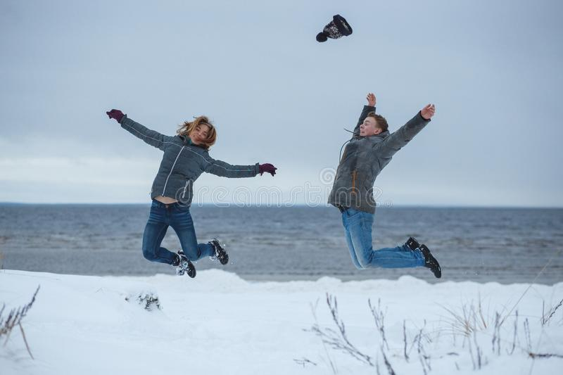 Young active couple joyful jumping up high together on winter holiday beach, nature outdoors. Fun energy recreational royalty free stock photo