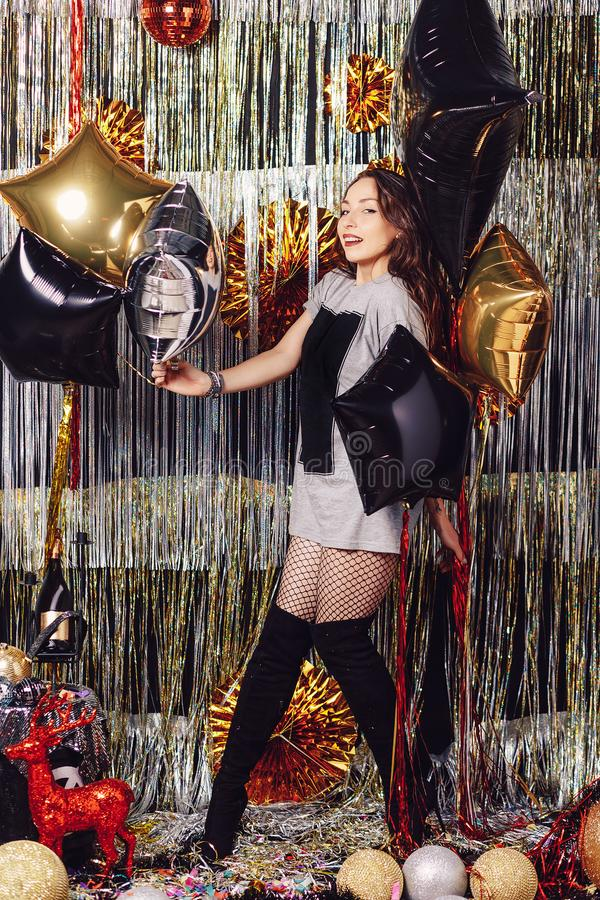Young dancing woman. Young active dancing woman on a shimmer background. Party hard. Girl holding balloons, ready to celebrate in a space with golden and silver royalty free stock photography