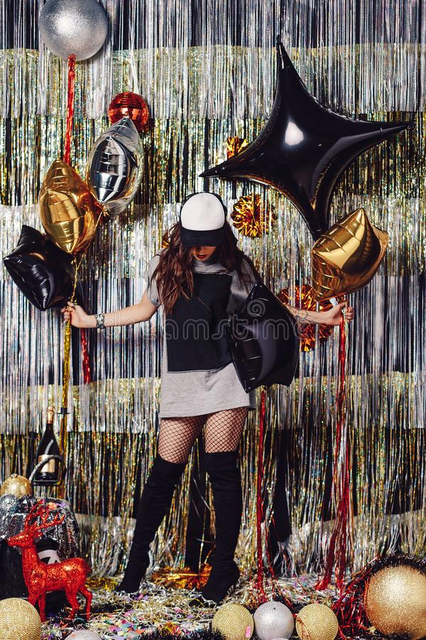 Young dancing woman. Young active dancing woman on a shimmer background. Party hard. Girl holding balloons, ready to celebrate in a space with golden and silver royalty free stock image