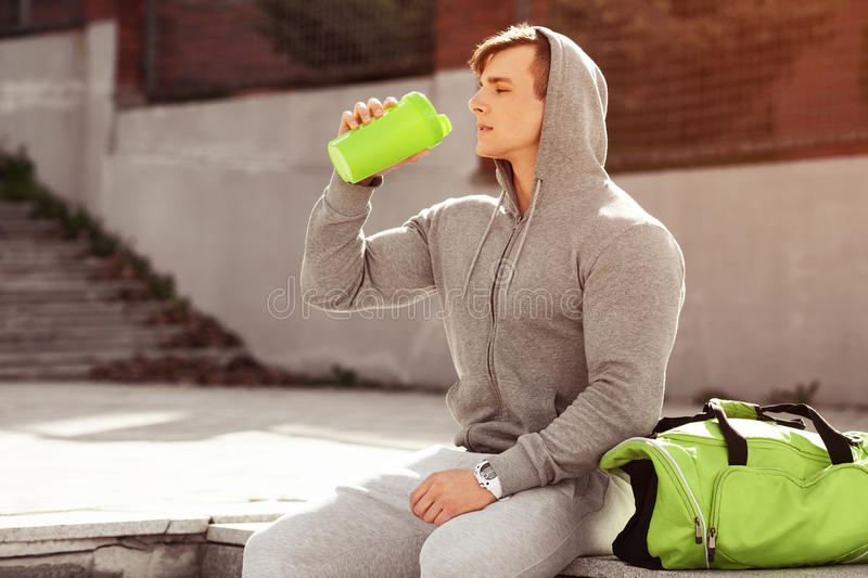 Young active man drinking water, outdoors. Handsome muscular male holding shaker royalty free stock image