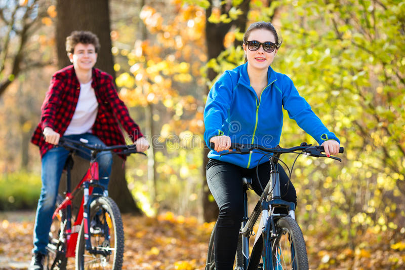 Young active people biking. Girl and boy biking in city park stock photography