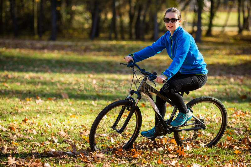 Young active people biking. Girl biking in city park royalty free stock photos