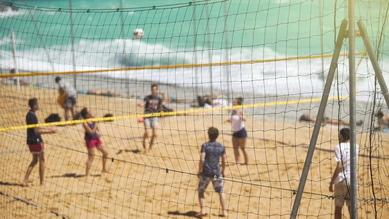 Young active people playing volleyball on sandy beach, team sport for friends stock image
