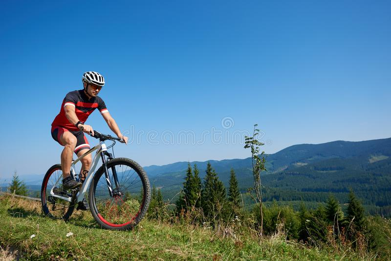 Cyclist in helmet, sunglasses and full equipment riding bike on grassy hill. Young active sportsman cyclist in helmet, sunglasses and full equipment riding bike royalty free stock image